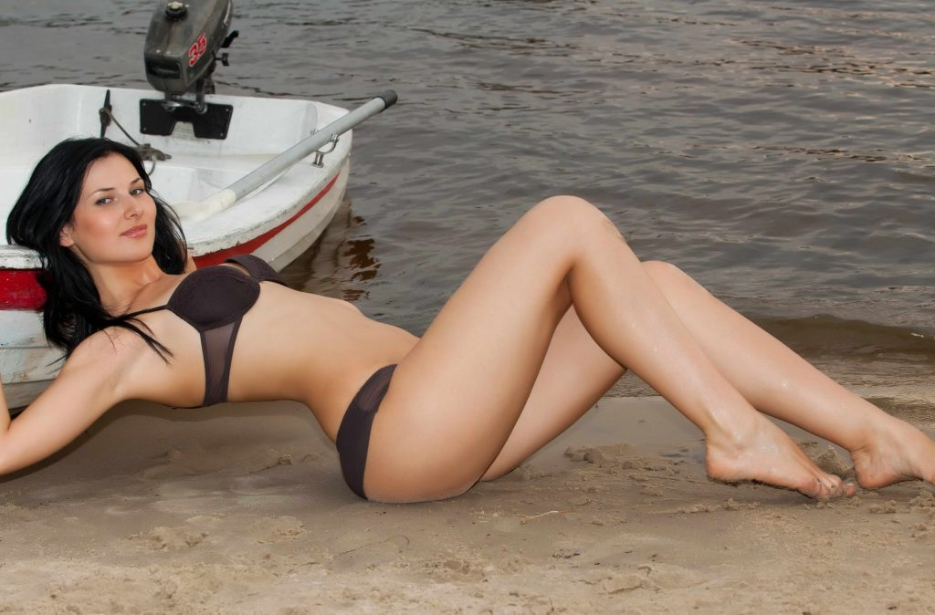 Young Brunette Stretching Legs on Beach